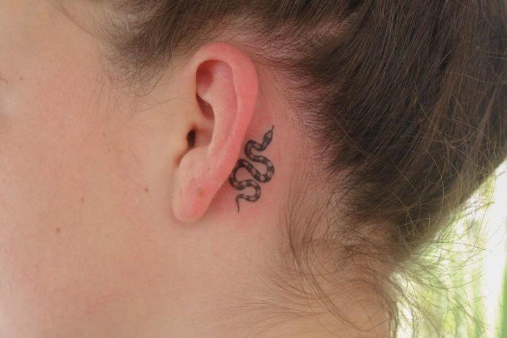 Tatuaje detrás de la oreja de una serpiente