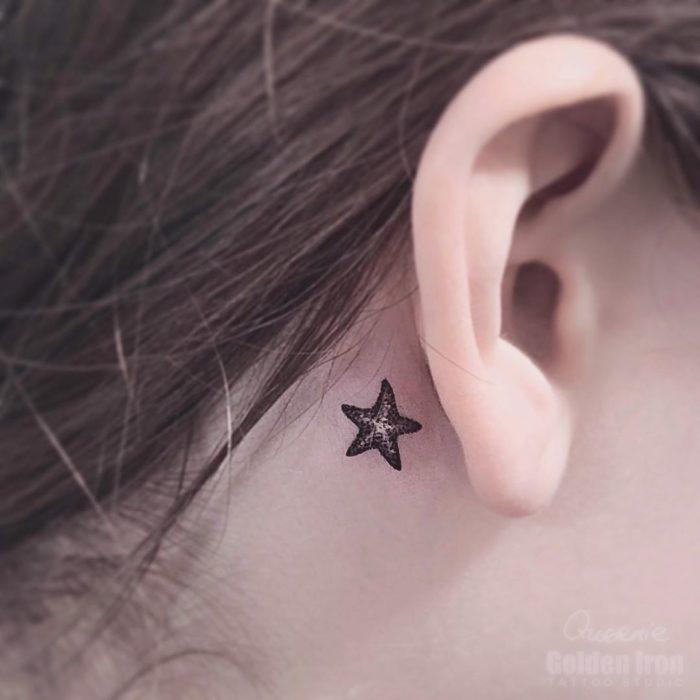 Tatuaje detrás de la oreja de una estrella de mar